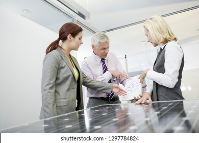 Businesspeople in office with solar panel studying alternative energy