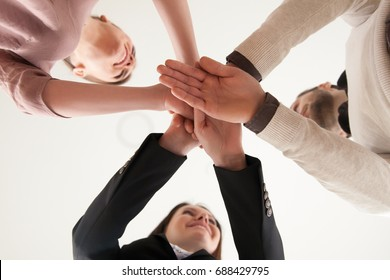 Businesspeople put hands on top of each other as symbol of team building, partnership, business ventures, firm intention to achieve success, working project, teamwork or unity concept, view from below