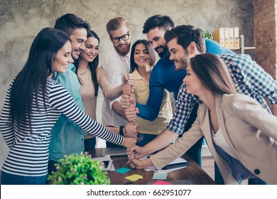Businesspeople putting their fists on top of each other on the desktop in nice light workstation, wearing casual clothes. Conception of successful team-building