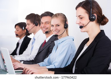 Businesspeople In A Row Wearing Headset Working At Office