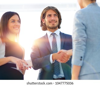 Businesspeople  shaking hands against room with large window loo