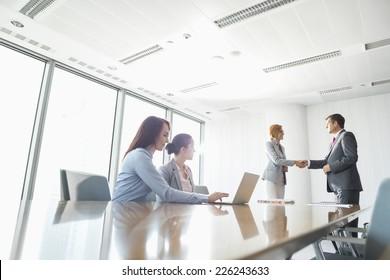 Businesspeople shaking hands in board room