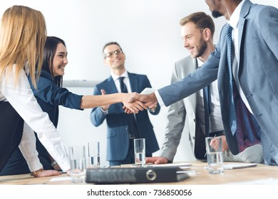 businesspeople shaking hands in conference hall