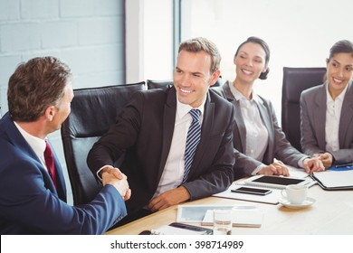 Businesspeople shaking hands in conference room during meeting