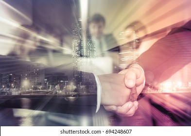 Businesspeople shaking hands on abstract city background