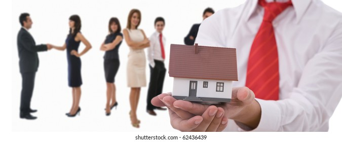 Businesspeople shaking hands and posing with dummy of house