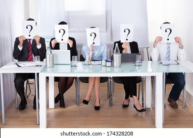 Businesspeople Sitting In Conference Room Holding Question Mark In Front Of Face