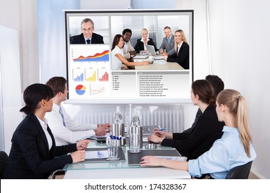 Businesspeople Sitting In A Conference Room Looking At Screen