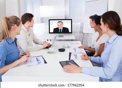 Businesspeople Sitting In Conference Room Looking At Monitor