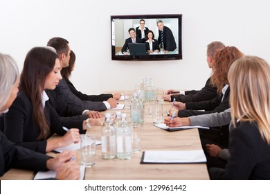 Businesspeople Sitting At Conference Table Looking At Flat Screen Display