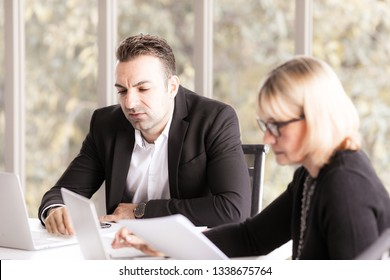 Businesspeople sitting at desk headed by serious concentrated male checking agreement document with senior businesswoman in eyeglasses.Serious woman listening to co-worker explaining  online busines.