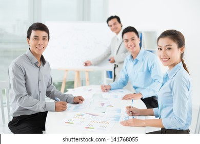 Businesspeople sitting at the meeting and looking at camera