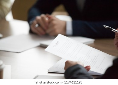 Businesspeople sitting office desk at meeting. Woman ceo holding pen and contract, ready to sign document, close up. Client, customer lease agreement buy sell real estate. Successful deal, hr concept