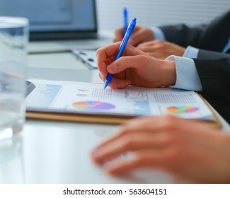 Businesspeople sitting on the desk in office