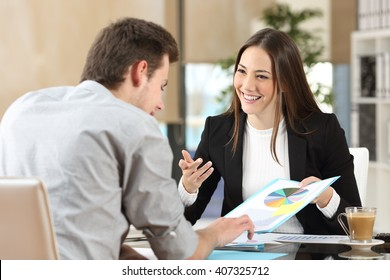 Businesspeople smiling coworking commenting and showing growth graphic and taking a business conversation in an office interior