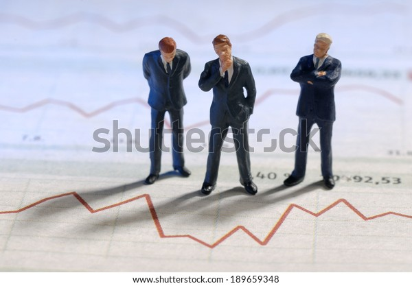Businesspeople are standing in front of of the graphic of a stock price.