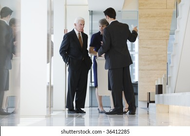 Businesspeople standing in a marbled corridor discussing plans.