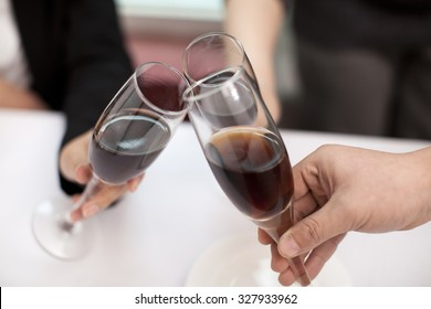 Businesspeople toasting glasses at restaurant table,close-up