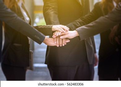 BusinessPeople unite their Hand as Stack to motivate group network or Team Spirit as Business Teamwork Concept