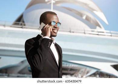 Businesspeople, urban lifestyle, modern technologies and communication concept. Joyful African CEO in trendy round shades and formal suit talking on smart phone outdoors on his way to office