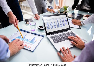 Businesspeople Using Calendar On Laptop While Analyzing Graphs Over Desk
