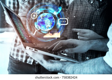Businesspeople using laptop with abstract digital hologram on blurry background. Close up. Teamwork and media concept. Double exposure. Elements of this image furnished by NASA