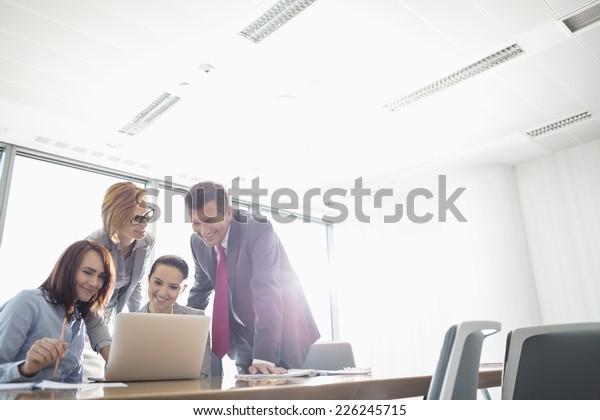Geschäftsleute, die Laptops am Konferenztisch nutzen