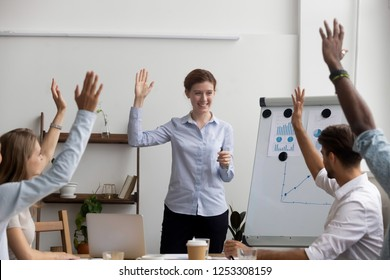 Businesspeople voting raise their hands think the same way, unanimously. Diverse multi-ethnic businesswomen businessmen gathered together in boardroom for training and business knowledge improvement