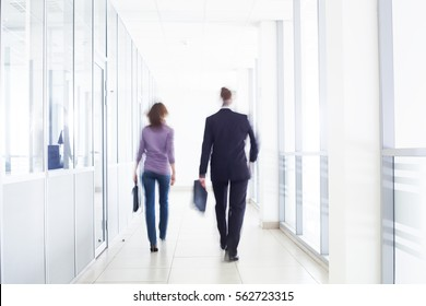businesspeople walking in the corridor of an business center, pronounced motion blur