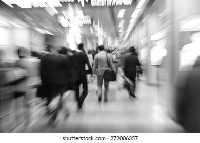 businesspeople walking in motion blur in a corridor
