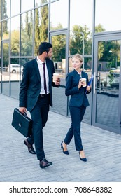 businesspeople walking outdoors with disposable cups of coffee