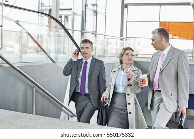 Businesspeople walking up stairs in train station