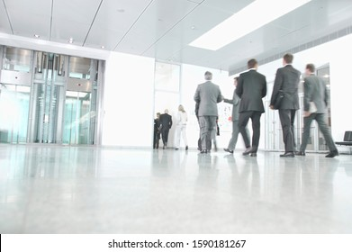 Businesspeople walking through office building