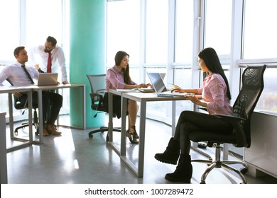 Businesspeople working as a team in office. Analyze papers and charts of new strartup. Business concept.