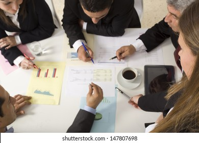 Businesspeople working together at meeting, discussing document