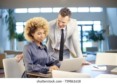 Businesspeople working together in the office. Young afro-american professional woman and senior financial director using laptop and consulting about new project.