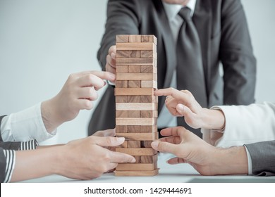 Businesspeople's hand is trying to hold a tower of wooden blocks game, Alternative risk and strategy in business concept