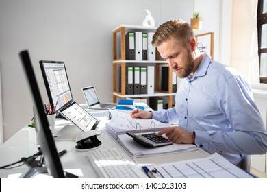 Businessperson Calculating Invoice With Computer On Desk