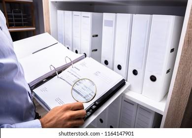 Businessperson Examining Bill In Folder Through Magnifying Glass