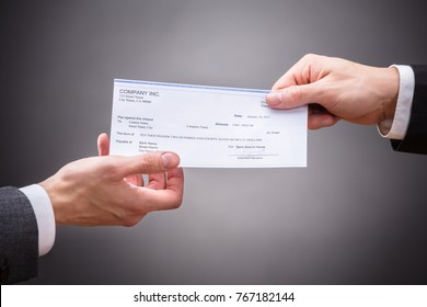 Businessperson Giving Cheque To Colleague On Grey Background