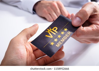 Businessperson Giving VIP Card To His Partner Over White Desk