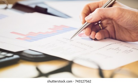 Businessperson inspecting a financial document with a pen in hand. Shallow DOF, focus on the paperwork.
