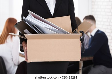Businessperson Leaving Office With Documents In Cardboard Box