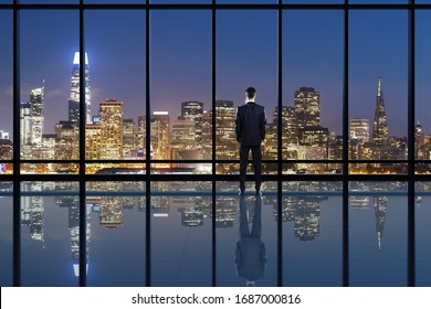 Businessperson looking into distance on rooftop with blurry night city view. Success, vision and future concept