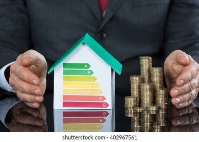 Businessperson Protecting House Model Showing Energy Efficiency Rate And Stack Of Coin On Desk