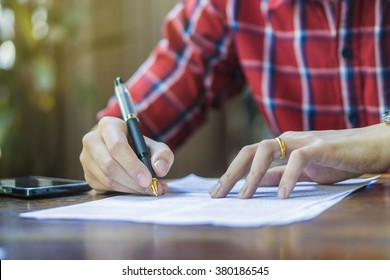 Businessperson Signing Contract,man writing paper at the desk with pen and reading books, Form filling petition agreement of divorce,morning light ,selective focus.copy space