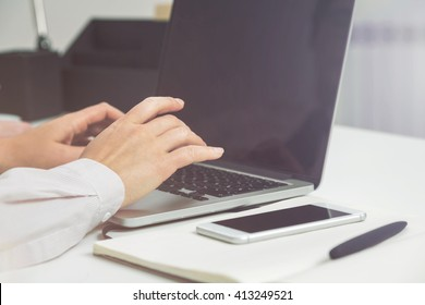 Businessperson using laptop with blank screen at white office desk. Mock up