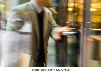 Businessperson walking through the revolving door in motion blur