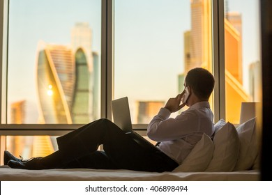 Businessperson working at home or in trip. Handsome young businessman sitting on bed with laptop and making call. Panoramic window with beautiful dawn city scenery on the background. Copy space