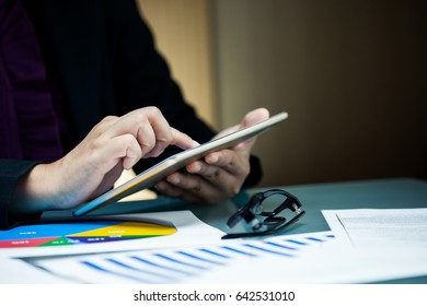 Businessperson working on digital tablet with graph data document on desk.